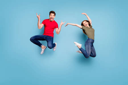 Full length photo of cheerful two people students man heavy metal lover show horns woman jump raise hands wear green red t-shirt denim jeans isolated blue color background Stockfoto - 134370580