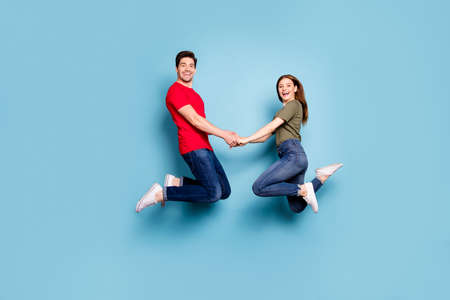 Full length profile side photo of charming two person woman man relax rest jump enjoy weekends hold hands wear green t-shirt denim jeans sneakers isolated over blue color background Stockfoto - 134370582