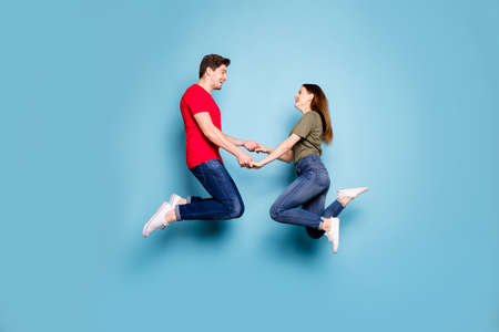 Full body profile side photo of charming two spouses relax rest on spring holidays jump hold hands feel content wear casual style clothes isolated over blue color background Stockfoto