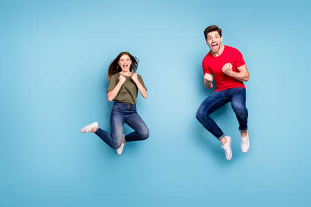 Full body photo of ecstatic two people spouses win lottery jump raise fists scream yeah wear green red t-shirt denim jeans sneakers isolated over blue color background Stockfoto