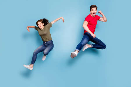 Full length photo of funky funny crazy two people students sportive team man woman jump practice fighting sport exercise kick hands wear casual style outfit isolated blue color background Stockfoto - 134370586