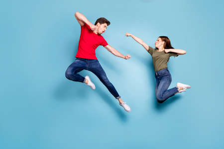 Full size photo of crazy man two people woman man spouses disagree jump fight kick boxing wear green red t-shirt denim jeans sneakers isolated over blue color background Stock Photo