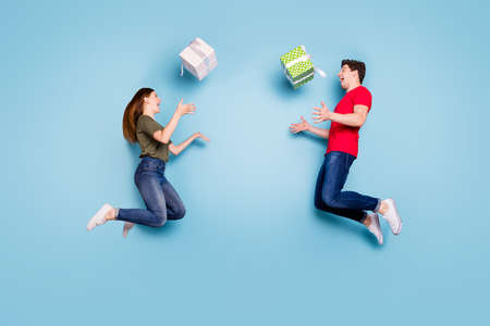 Full length profile side photo of two crazy married people students celebrate 14-february jump holiday throw gift box falling wear casual style clothing sneakers isolated blue color background Stockfoto