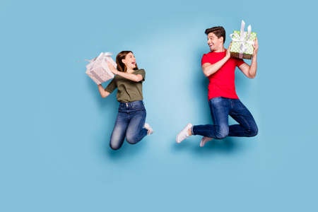 Full length profile side photo of funny crazy two people spouse romantic date on 14-february get gift boxes rejoice jump wear denim jeans red green t-shirt isolated blue color background
