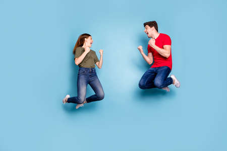 Yeah lucky win. Full length profile side photo of crazy funky delighted two married people jump celebrate lottery victory raise fists scream wear modern denim isolated blue color background Stockfoto
