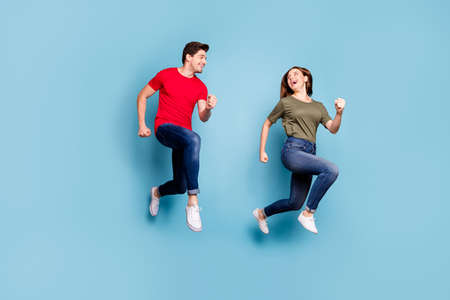Full length photo of charming spouses relax rest jump run wear green red t-shirt denim jeans sneakers isolated over blue color background Stockfoto - 134370619