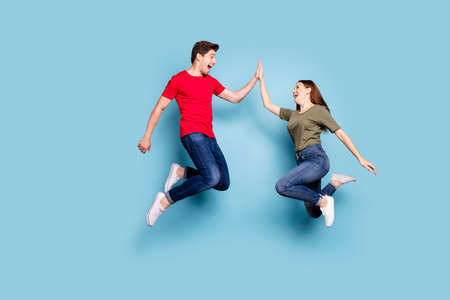 Great job. Full length profile side photo of cheerful two romantic people jump give highfive celebrate victory wear modern t-shirt denim jeans sneakers isolated blue color background Stockfoto