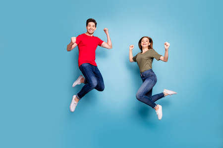 Full body photo of brown redhair romantic couple jump show biceps triceps enjoy power wear modern youth outfit isolated over blue color background Stockfoto - 134370625