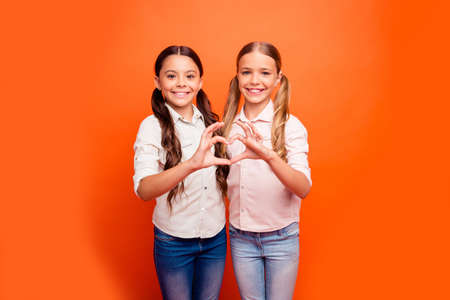 Portrait of positive cheerful two kids girl stand together make heart fingers sign of friendly loving family sister relationship wear casual clothing isolated orange color background