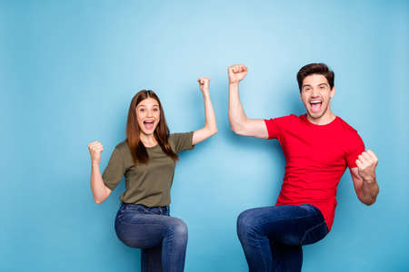 Portrait of romantic couple celebrate victory scream yeah raise fists feel rejoice wear green red t-shirt denim isolated over blue color background Stok Fotoğraf