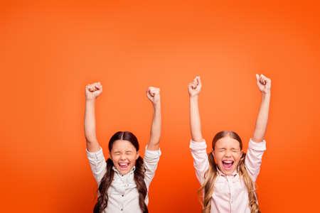 Ja ongelooflijke overwinning. Portret van gelukkige opgetogen gekke twee kinderen meisjes winnen wedstrijd voelen euforie schreeuwen vuisten opheffen dragen moderne kleding geïsoleerde oranje kleur achtergrond Stockfoto