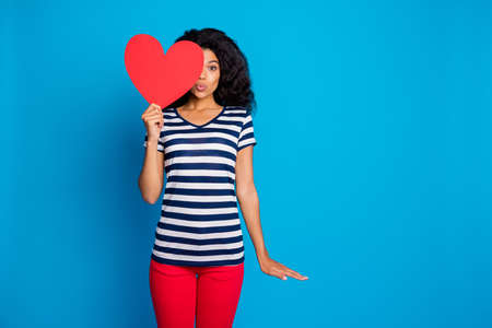 Photo of nice sweet girlfriend curly wavy haired kissing you through air wear, striped t-shirt pants trousers half of face with big red heart isolated near empty space blue vibrant color background Stock fotó