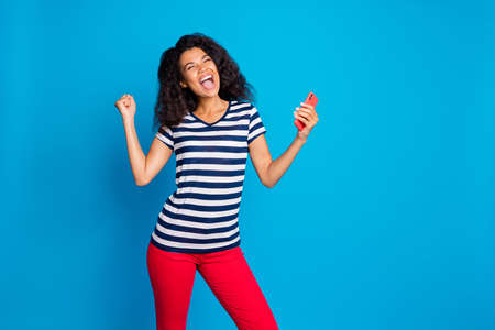 Portrait of delighted mulatto girl hold cellphone read social network, news got like jackpot victory raise fists scream yeah wear striped t-shirt red pants trousers isolated blue color background Banco de Imagens