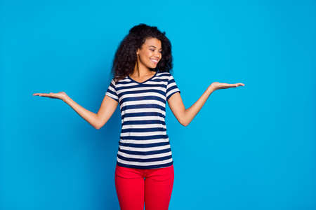 Photo of cheerful positive casual curly wavy girlfriend holding two objects, showing you advantages of one side in striped t-shirt isolated vivid color blue background