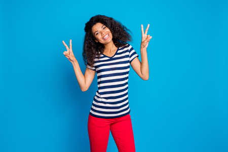 Photo of cheerful positive cute pretty nice charming girlfriend showing double v-sign smiling toothily showing her friendly facial expression, isolated blue vibrant color background Standard-Bild