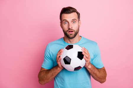 Photo of amazed surprised man in stupor holding soccer ball with hands, loving to play football isolated pastel color background