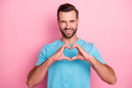 Photo of cheerful positive, attractive man showing you heart sign shaped with fingers to show his love to you isolated pastel color background