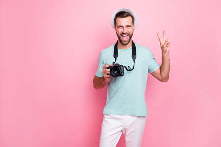Portrait of funky funny man tourism lover have spring vacation hold dlsr professional camera, make v-sign wear blue t-shirt white pants isolated over pink color background
