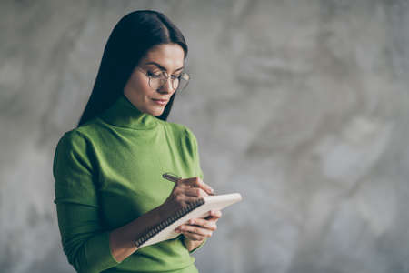 Photo of serious confident woman noting down information heard from employee holding copybook writing with pen isolated concrete grey color background