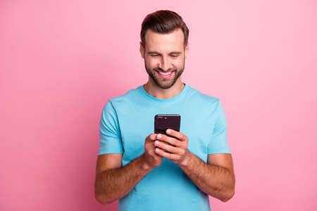 Photo of trendy cheerful positive smm manager browsing through telephone in search of ways to update operating system isolated pastel color background Stock Photo