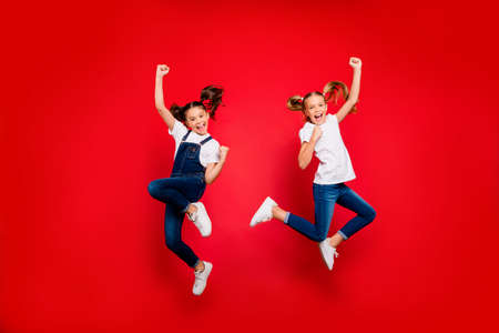 Full length photo of cheerful two small little people girlfriends celebrate triumph raise fists scream yes jump wear white t-shirt denim jeans sneakers isolated bright color background