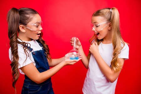 Photo of two beautiful little ladies diligent school children make chemical experiment excited results hold tube wear jeans overall white t-shirt isolated red color background Imagens