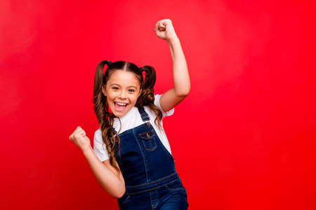 its christmas time. Photo of beautiful little lady positive mood newyear holidays raising fists last studying day wear casual jeans overall white t-shirt isolated red color background