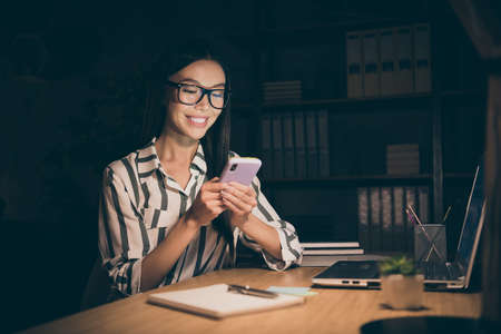 Photo of pretty chinese business lady holding telephone reading sms working late at night have little break toothy smiling sit chair wear striped shirt dark modern office