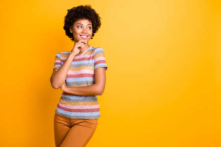 Photo of wavy cheerful positive toothy beaming beautiful girlfriend wearing striped t-shirt touching her chin looking into empty space isolated over yellow vivid color background