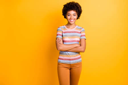 Photo of amazing dark skin business lady holding arms crossed ready for new duty wear casual striped t-shirt and trousers isolated on yellow background
