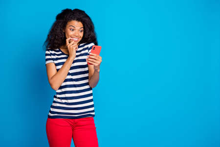 Photo of cheerful positive nice pretty youngster browsing through phone having received new sms rejoicing her smiling toothily biting nails near empty space isolated blue vivid color background