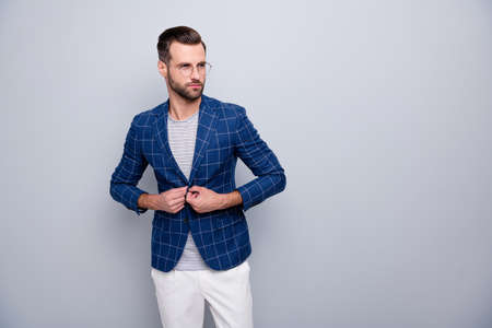 Portrait of his he nice elegant chic classy serious attractive well-dressed imposing bearded guy wearing checked blazer fixing button isolated over light grey pastel color background