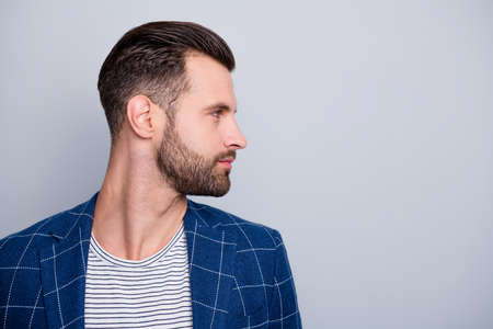 Photo of man looking into empty space showing the result of his hairstylist work with bristle on face turning head side profile isolated grey color background