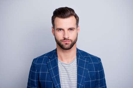 Retrato de primer plano de su agradable chico barbudo tranquilo, serio, atractivo, bien arreglado, vistiendo blazer a cuadros aislado sobre fondo de color pastel gris claro