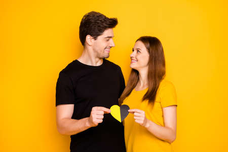 Photo of cheerful cute charming pretty couple of beautiful people looking at each other affectionately embracing holding multicolor heart symbolizing love isolated vivid color background Stock Photo