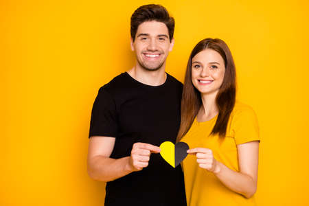 Photo of trendy cheerful cute nice charming pretty couple of two spouses holding t-shirt heart shape to show their love hugging isolated over vibrant shiny color background