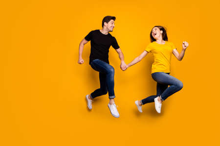 Full size photo of funny guy and lady couple jumping high rushing mall black friday final discounts season wear casual jeans black t-shirts isolated yellow color background