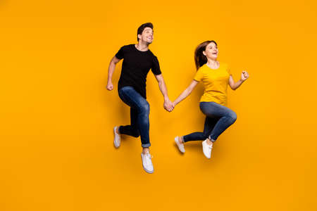 Full size photo of sporty guy and lady couple jumping high holding hands pair speed marathon participants wear casual jeans t-shirts isolated yellow color background Archivio Fotografico