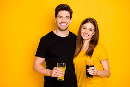 Photo of cheerful cute nice charming pretty sweet couple hugging holding glasses filled with cold summer beverages wearing black t-shirt isolated over vivid color background