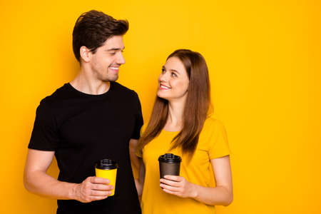 Photo of cheerful positive fun cute nice pretty couple of two spouses hugging while drinking hot beverage isolated in black t-shirt over yellow vibrant shiny color background