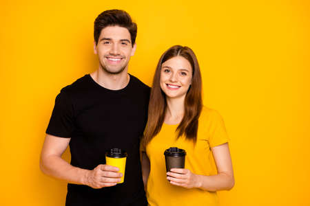 Photo of pretty sweet cute nice couple of two spouses holding mugs filled with hot beverage hugging smiling toothily in black t-shirt isolated over vivid color background Stock Photo