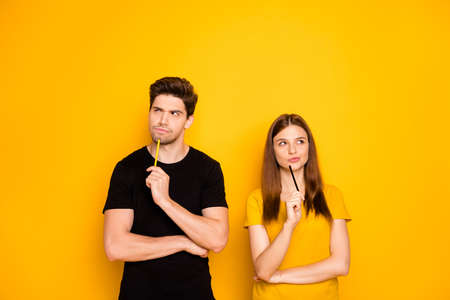 Photo of serious confident couple of two people interested in thinking over standing under empty space holding pens wearing black t-shirt isolated over vivid yellow color background