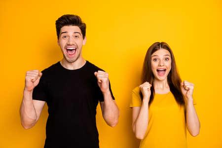 Foto de alegre positivo emocionado linda pareja divertida regocijándose sobre el evento victorioso gritando gritando en camiseta negra aislado fondo de color brillante