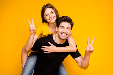 Photo of cheerful cute charming positive nice couple showing you v-sign wearing black t-shirt jeans denim piggyback isolated over vivid color background Stock Photo