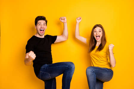 Photo of crazy screaming overjoyed rejoicing couple wearing jeans denim black t-shirt stylish going mad about winning sport competitions isolated yellow bright shine color background 免版税图像