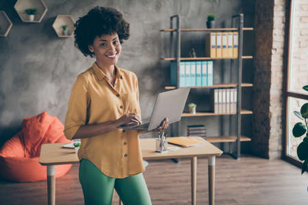 Portrait of cool afro american girl start-up entrepreneur hold computer leadership watch work seminar concept wear yellow shirt green pants trousers stand in workstation office loft