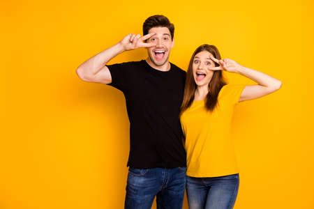 Photo of cheerful cute pretty sweet beautiful couple showing you v-signs wearing jeans denim black t-shirt expressing ecstatic emotions isolated over shiny bright color background