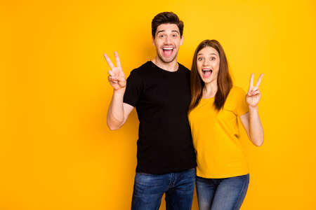 Photo of cheerful fascinating pretty gorgeous couple wearing jeans denim black t-shirt showing double v-sign with excited facial expressions isolated over vivid color yellow background