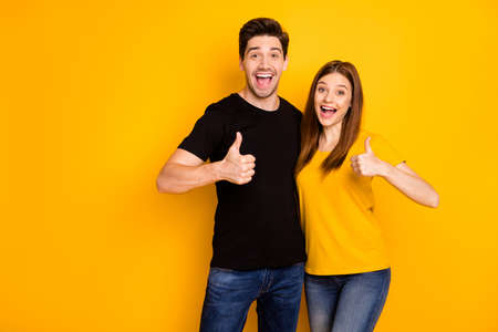Photo of positive cheerful cute charming girlfriend and boyfriend showing their thumbs up wearing jeans denim black t-shrit expressing kind emotions giving feedback isolated vibrant color background