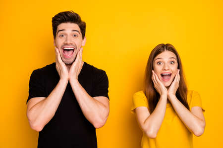 Photo of cheerful positive cute charming beautiful nice couple excited about sales started with man wearing black t-shirt isolated over vivid color background